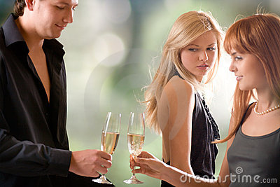 Young couple holding glasses with champagne and woman looking at