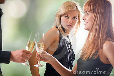 Young couple holding glasses with champagne and woman looking