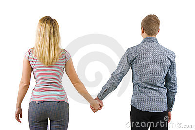A young couple holding hands, back to camera