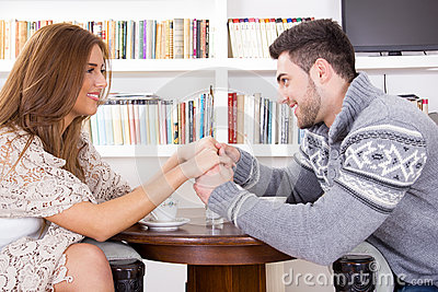 Young couple holding hands in the living room stock photo for Young couple living room ideas