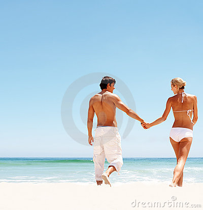 Young couple holding hands and walking in t