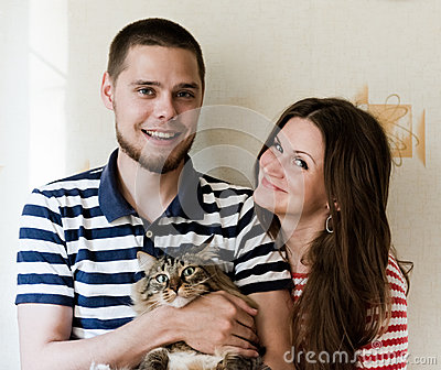 Young couple at home with their cat