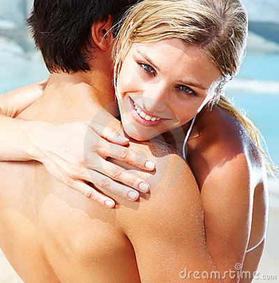 Young couple hugging eachother on the beach