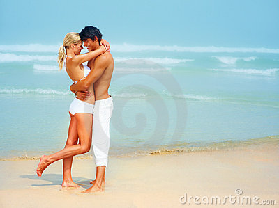 Young couple hugging eachother at the beach