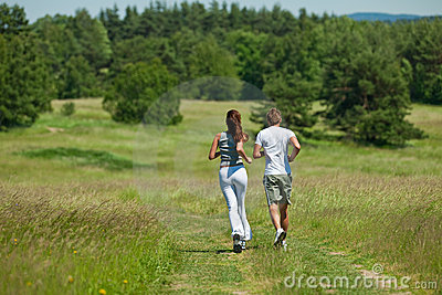 Young couple jogging outdoors in summer