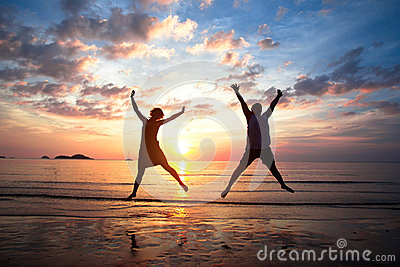 Young couple in a jump on the sea beach at sunset