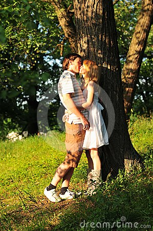 Young couple kiss outdoors in the forest