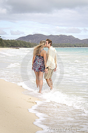 A young couple kiss in the waves