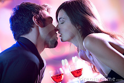 Young lovers kissing in restaurant, celebrating or on romantic d
