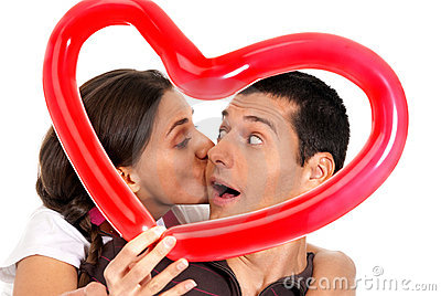Young couple kissing balloon heart surprise