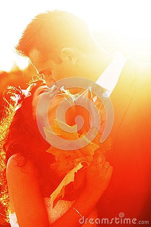 Young couple kissing at bright sunset
