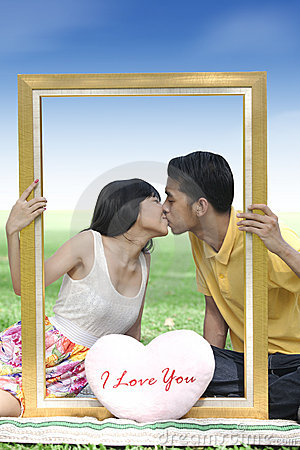 Young couple kissing with a frame