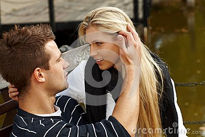 Young couple kissing by lake