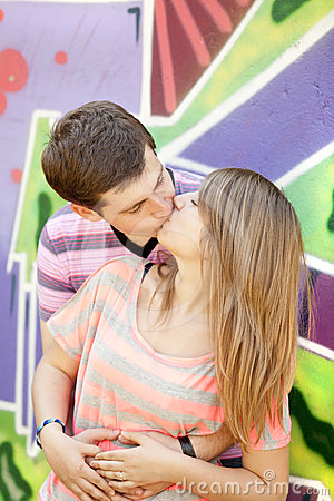 Young couple kissing near graffiti background.