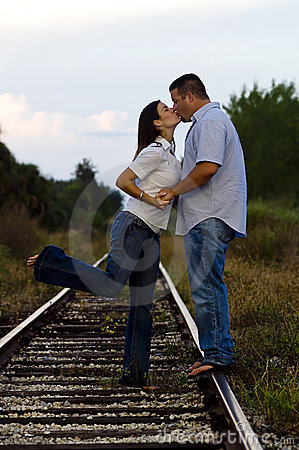 Young couple kissing on rail tracks