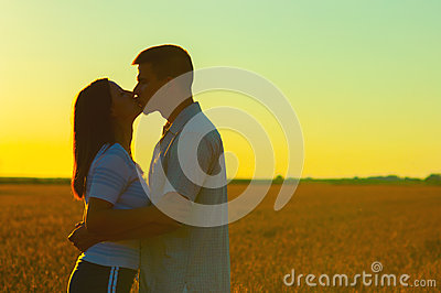 Young couple kissing on the wheat field
