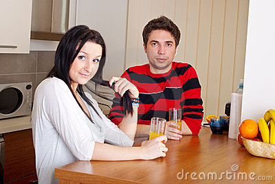 Young couple in kitchen drink juice