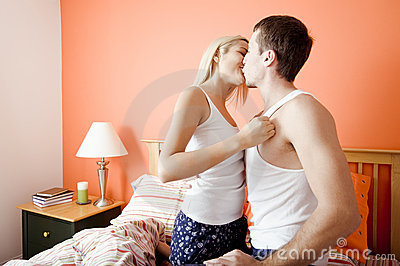 Young Couple Kneeling on Bed Kissing
