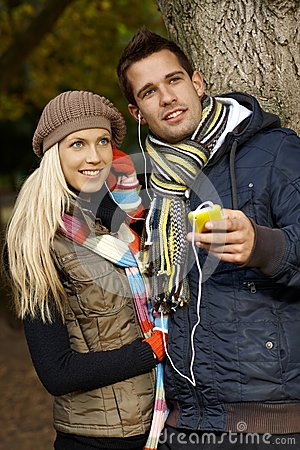 Young couple listening to music outdoors smiling