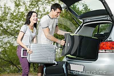 Young couple loading suitcases in the car boot