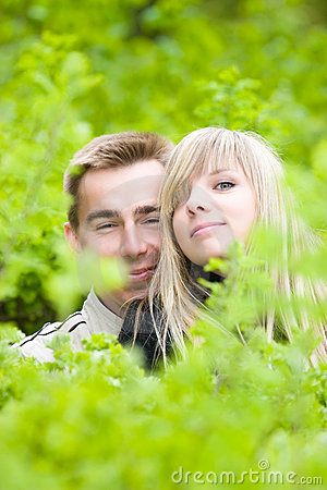 Young couple look out of green bushes