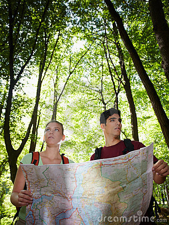 Young couple looking at map during trek