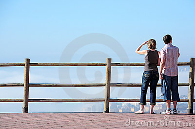 Young couple looking out to sea from high viewpoint