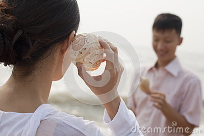 Young couple looking at seashells, holding shell to ear