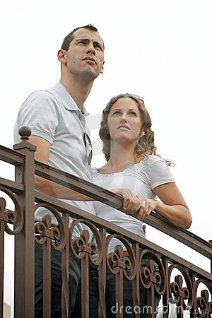 Young couple looking up to the sky from outside ba