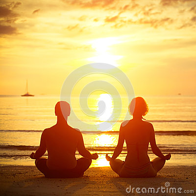 Young couple in a lotus position meditating on the beach