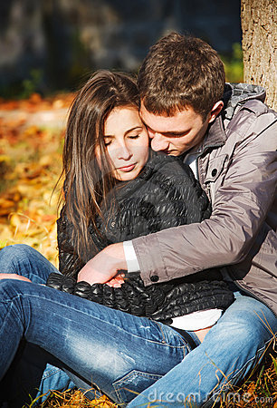 Young couple in love hugging in park
