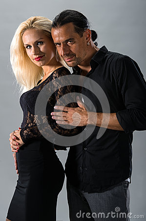 Young couple in love posing in studio dressed in classic clothes