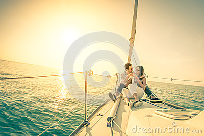 Young couple in love on sail boat with champagne at sunset