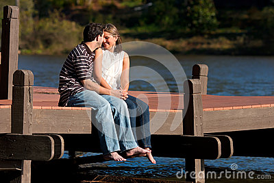 Young Couple In Love Sit Barefoot On Dock