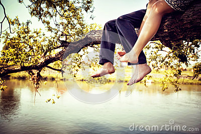 Young couple in love sitting cross-legged on a tree branch above the river in nice sunny day. Photo is colorized in warm tints Stock Photo