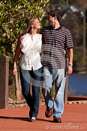 Young Couple In Love Walk By A Lake