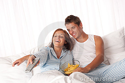 Young couple lying down in white bed