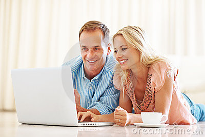 Young couple lying on floor using a laptop