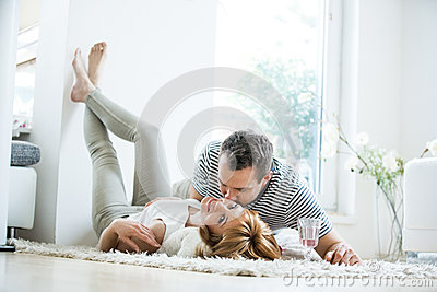 Young couple lying in living room on carpet stock photo for Living room ideas young couples