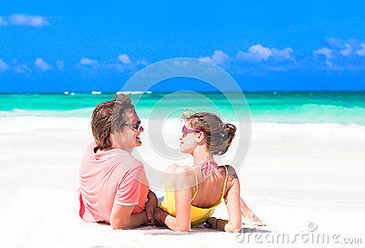 Young couple lying on sand under sunny summer sun