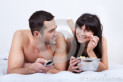 Young couple lying up in bed and watching TV