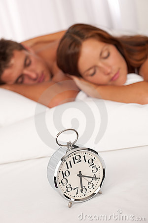 Young couple lying in white bed with alarm clock