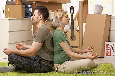 Young couple meditating in new house