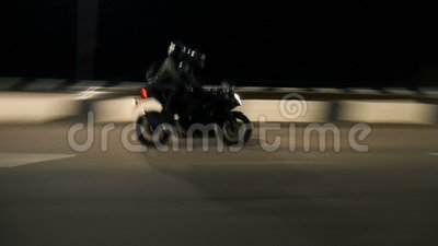Young couple of motorcyclists riding on a night road. stock footage