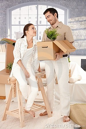 Young couple moving home unpacking boxes