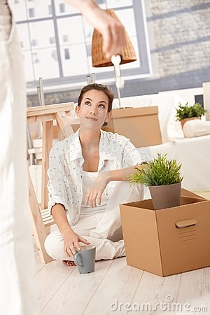 Young couple moving home woman sitting with boxes