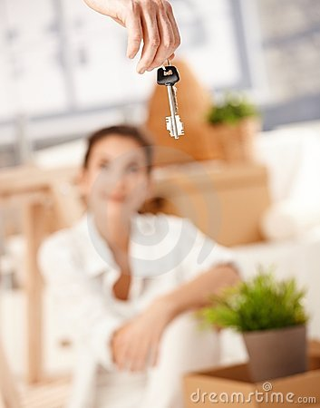 Young couple moving to new house keys hanging