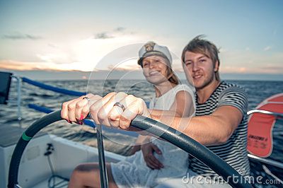 Young couple navigating on a yacht