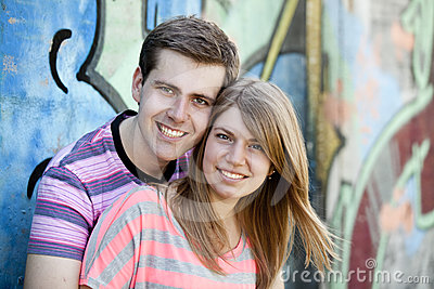 Young couple near graffiti background.