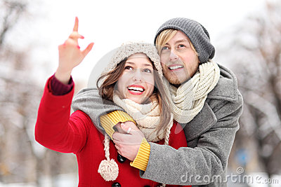 Young couple outdoors, woman pointing